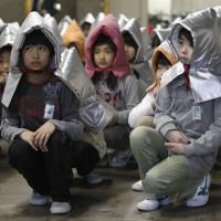 Children in padded hoods take part in a disaster drill named 'Shakeout Tokyo' at Izumi Elementary School in March 2012. | REUTERS
