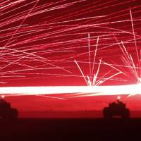 Tracer bullets ricochet off their targets as Ground Self-Defense Force tanks fire their machine guns during a night session of an annual training exercise at Higashifuji training field near Mount Fuji in Gotemba, Shizuoka Prefecture, on Tuesday.   REUTERS