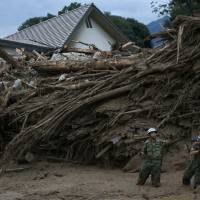 Self-Defense Forces soldiers search for survivors at a site where a landslide swept through a residential area in Asaminami Ward in Hiroshima on Aug. 20.    REUTERS
