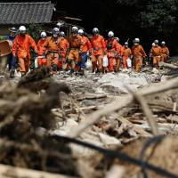 Firefighters search for survivors Saturday following a series of landslides that tore through a residential neighborhood of Asaminami Ward, Hiroshima, last week. | REUTERS