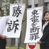 Lawyers representing the family of a woman who committed suicide in the wake of the Fukushima nuclear disaster show off banners saying 'Victory' and 'Tepco is guilty' after a court ruling in favor of the plaintiffs Tuesday in front of the Fukushima District Court. | KYODO