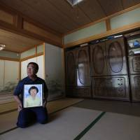 Mikio Watanabe holds a portrait of his late wife, Hamako, at his home in the Yamakiya district of Kawamata, Fukushima Prefecture, on June 23. A Fukushima district court has ruled that Tokyo Electric Power Co. was responsible for Hamako's suicide following the March 2011 nuclear disaster and must pay ¥49 million yen in compensation. | REUTERS