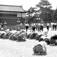 People prostrate themselves as they listen to Emperor Hirohito's radio broadcast announcing Japan's surrender in World War II, outside the Imperial Palace in Tokyo, on Aug. 15, 1945. | KYODO
