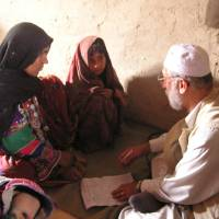 Khaled Reshad provides health advice to a woman and a girl during a visit to a village, which at the time had no resident doctor, in rural Afghanistan in May 2004. | COURTESY OF KHALED RESHAD