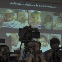 Thai police display pictures of surrogate babies born to a Japanese man who is at the center of a surrogacy scandal, during a news conference at police headquarters in Chonburi on Aug. 12. Interpol said Friday it has launched a multinational investigation into what Thailand has dubbed the 'Baby Factory' case: a 24-year-old Japanese businessman who has 16 surrogate babies and an alleged desire to father hundreds more. | AP