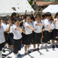 Children release butterflies during a memorial service held in Naha on Friday in memory of passengers who died aboard the Tsushima Maru. The Japanese ship, carrying hundreds of schoolchildren, sank in 1944 following a U.S. torpedo attack. | KYODO
