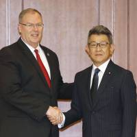 U.S. Deputy Secretary of Defense Robert Work shakes hands Friday with Ryota Takeda, parliamentary senior vice minister of defense, at the Defense Ministry before holding talks.   KYODO