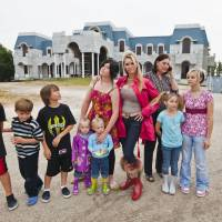 Larger than life: Jackie Siegel (center), surrounded by her eight children in front of their unfinished home. Filmmaker Lauren Greenfield followed the billionaire family through the 2008 financial crisis. | © 2012 QUEEN OF VERSAILLES, LLC. ALL RIGHTS RESERVED