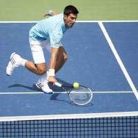 On the run: Novak Djokovic plays a shot from France's Gael Monfils in their second-round match at the Rogers Cup in Toronto on Wednesday. Djokovic won 6-2, 6-7 (4-7), 7-6 (7-2). | AP