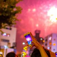 Explosive change: Smartphones are one of the many products that have drastically altered daily life for Japanese. | 'TAKING PHOTOS OF FIREWORKS' BY YOSHIKAZU TAKADA; USED UNDER CC BY-SA 2.0