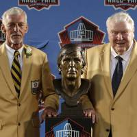 Historic moment: Hall of Fame inductee Ray Guy (left) and presenter John Madden stand beside Guy's bust at the induction ceremony on Saturday. Guy, who was part of three Super Bowl championship teams with the Raiders, is the first punter to make the Hall. | AP