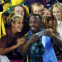Come together: Usain Bolt poses for pictures with fans at the Commonwealth Games on Saturday. | REUTERS
