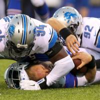 Look out below: Bills quarterback Jordan Palmer loses his helmet while being brought down by the Lions' Devin Taylor (94) and Ezekiel Ansah (92) on Thursday. Detroit beat Buffalo 23-0. | AP