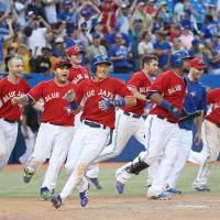 That took awhile: Munenori Kawasaki (center) begins to celebrate with the rest of the Blue Jays after scoring the winning run against the Tigers during the 19th inning on Sunday. | KYODO