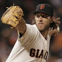 Oh so close: Giants starter Madison Bumgarner pitches against the Rockies on Tuesday in San Francisco. Bumgarner carried a perfect game into the eighth inning before allowing a leadoff single to Justin Mourneau. | AP