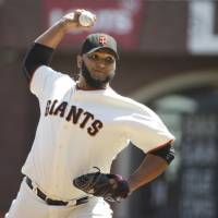 Mowing them down: Giants pitcher Yusmeiro Petit delivers agianst the Rockies on Thursday in San Francisco. | AP