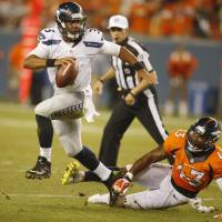 Elusive: Seattle QB Russell Wilson scrambles away from Denver's T.J. Ward in the first half of their preseason opener on Thursday night. The Broncos won 21-16. | REUTERS/USA TODAY SPORTS