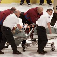 Resolution: Steve Moore is taken off the ice on after being punched by Todd Bertuzzi during a game on March 8, 2004. | AP