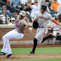 Wild pitch: San Francisco's Hunter Pence scores as New York reliever Jeurys Familia reaches for the ball in the seventh inning. | AP