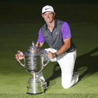Taking home the hardware: Rory McIlroy poses with the trophy after winning the PGA Championship on Sunday. | REUTERS