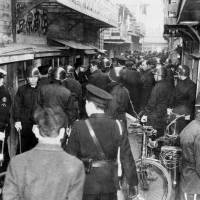 Drug epidemic: Police search an alley in Tokyo's Okachimachi district after apprehending a suspect carrying methamphetamine in January 1953. | KYODO