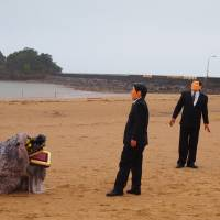 Protesters dressed as Prime Minister Shinzo Abe and Liberal Democratic Party Secretary-General Shigeru Ishiba are confronted by a shīsa during Mao Ishikawa's photoshoot. | JON MITCHELL