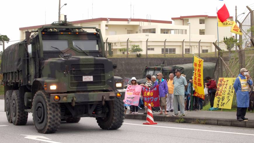 A military truck passes protesters outside Marine Corps Camp Schwab in June. | JON MITCHELL