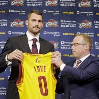 Love is in the air: Kevin Love holds his new jersey alongside Cavs general manager David Griffin at the team's practice facility in Independence, Ohio, on Tuesday.   AP