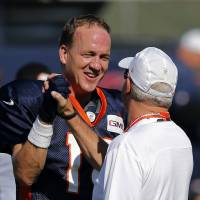 It's just a game: Peyton Manning (left) shakes hands with Broncos coach John Fox at training camp on Tuesday. | AP
