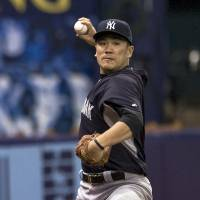 Passes test: Masahiro Tanaka throws as Yankees pitching coach Larry Rothschild looks on Saturday in St. Petersburg, Florida. | AP