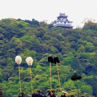 Pom-pom procession: People in traditional costume walk across Kintaikyo Bridge, with Iwakuni Castle in the background. | ANGELES MARIN CABELLO