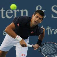No joke: Novak Djokovic serves to Giles Simon during his first match at the Western & Southern Open on Tuesday. | AP