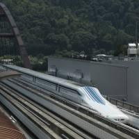 Back track: An L0 (L zero) Series magnetically levitated train moves along a test track during a trial run in Tsuru, Yamanashi Prefecture, last year. | BLOOMBERG