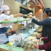 Make the healthy choice: Two young women get lunch at a university cafeteria in Tokyo. | KYODO