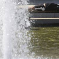 Weather extremes: A man lies in the sun near a water fountain on Aug. 6. | AP