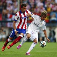 City divided: Atletico Madrid striker Mario Mandzukic (left) competes with Real Madrid's Fabio Coentrao during the Spanish Super Cup second leg on Friday. | REUTERS