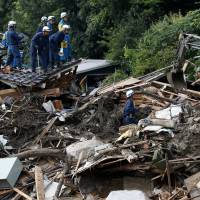 Volunteers sought: Police officers and a Self-Defense Force soldier search for landslide survivors amid the debris in Asaminami Ward, Hiroshima, on Saturday. | REUTERS
