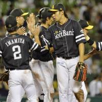 All in the family: The Hawks celebrate after their win over the Lions on Tuesday.   KYODO
