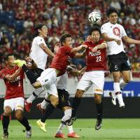Take me higher: Vissel's Hiroyuki Komoto (far right) launches a header at the Urawa goal during the teams' 2-2 draw on Saturday. | KYODO