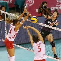 In the middle of the action: Japan's Kana Ono spikes the ball as two Turkey players converge at the net during Thursday's FIVB World Grand Prix Finals match at Ariake Colosseum. Japan defeated Turkey 25-13, 25-17, 25-17. | FIVB
