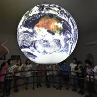 Local elementary school students look at the Science On a Sphere displaying planetary data at the Discovery Center in Higashimatsushima, Miyagi Prefecture, on July 26.    KYODO