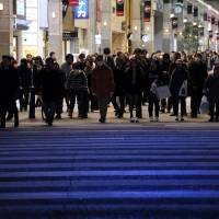 Pedestrians wait to cross an intersection at a shopping street in Sendai. Prime Minister Shinzo Abe's economic policy, dubbed 'Abenomics,' appears to be faltering, with no magic solution in sight. | BLOOMBERG