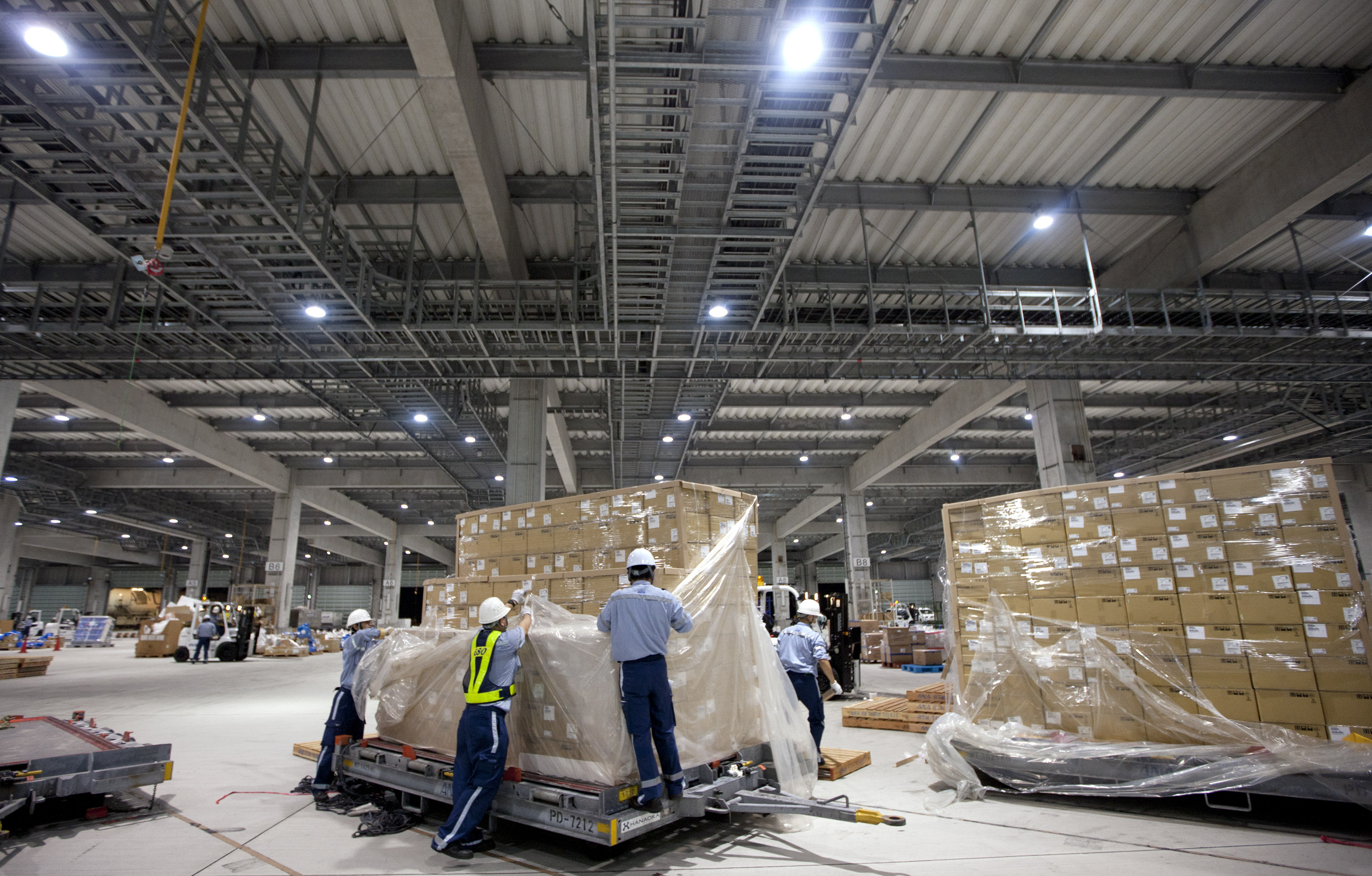 Workers sort packages at All Nippon Airways Co.'s cargo hub terminal at Naha Airport in Okinawa Prefecture. ANA Holdings Inc. and Deutsche Lufthansa AG have announced plans for the launch of a joint air shipping service.   BLOOMBERG