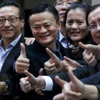 Alibaba Group Holding Ltd. founder Jack Ma (second from left) gives the thumbs-up sign as he arrives at the New York Stock Exchange for his company's initial public offering under the ticker 'BABA' in New York on Friday. | REUTERS
