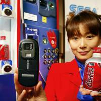 In June 2004, a Coca-Cola Japan employee in Tokyo holds up a phone equipped with Sony's NFC technology FeliCa for making purchases from vending machines. | AFP-JIJI