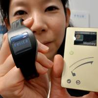 A Sony prototype is displayed of a new smart card with an NFC chip that has a FeliCa device in Tokyo in July. | AFP-JIJI
