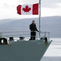 Canadian Prime Minister Stephen Harper stands on the bow of the HMCS Kingston as it sails in the Navy Board Inlet, Nunavut, on Aug. 24. | AP
