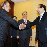 Fujio Cho (left), Toyota Motor Corp.'s honorary chairman, is greeted by Chinese Commerce Minister Gao Hucheng in Beijing on Tuesday as Sadayuki Sakakibara (center), head of the Keidanren business lobby, looks on.   KYODO
