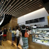 Customers order food and drinks at a counter in the Rakuten Cafe in Tokyo on May 29. Companies across the nation are revamping their offerings as the government attempts to boost female participation in the workforce. | BLOOMBERG