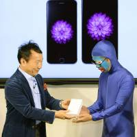 Kaoru Kato (left), president of NTT Docomo Inc., hands an Apple Inc. iPhone 6 to the first customer in line in Tokyo's Yurakucho district on Friday. | KYODO